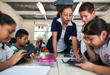 A group of elementary school kids work together at a table, while their teacher leans over to help a student with their device.