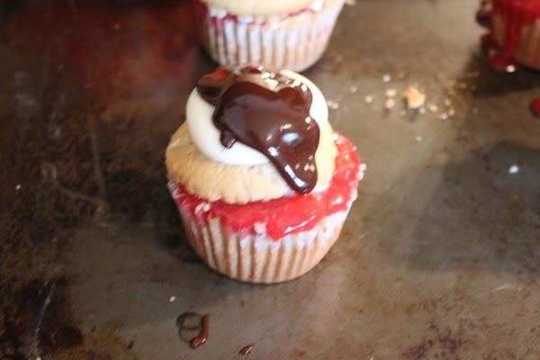 Adding frosting and chocolate to cupcake.