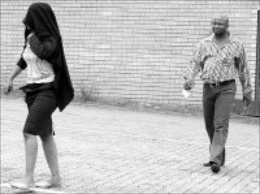 COVER BLOWN: A testing station official is led away by organised crime unit spokesman Leonard Hlathi after she was arrewsted at her Mbombela office yesterday. Pic. Andrew Hlongwane. © Sowetan.