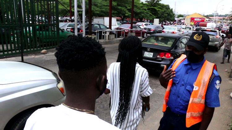 Abubakar, security man at Wuse Market, Abuja ensuring compliance of COVID-19 protocol.