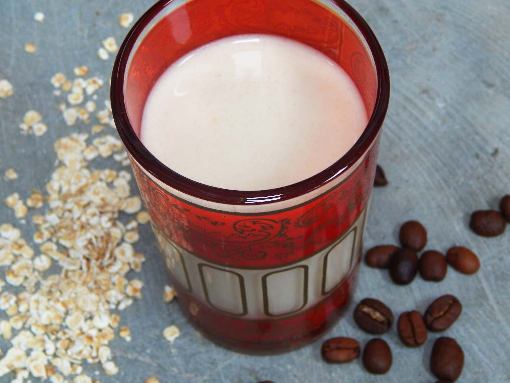 Oat milk in a glass with coffee beans and scattered oats