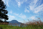 View of Annette Island from near Ketchikan, Alaska. Whispy clouds and blue sky. Summer grasses...