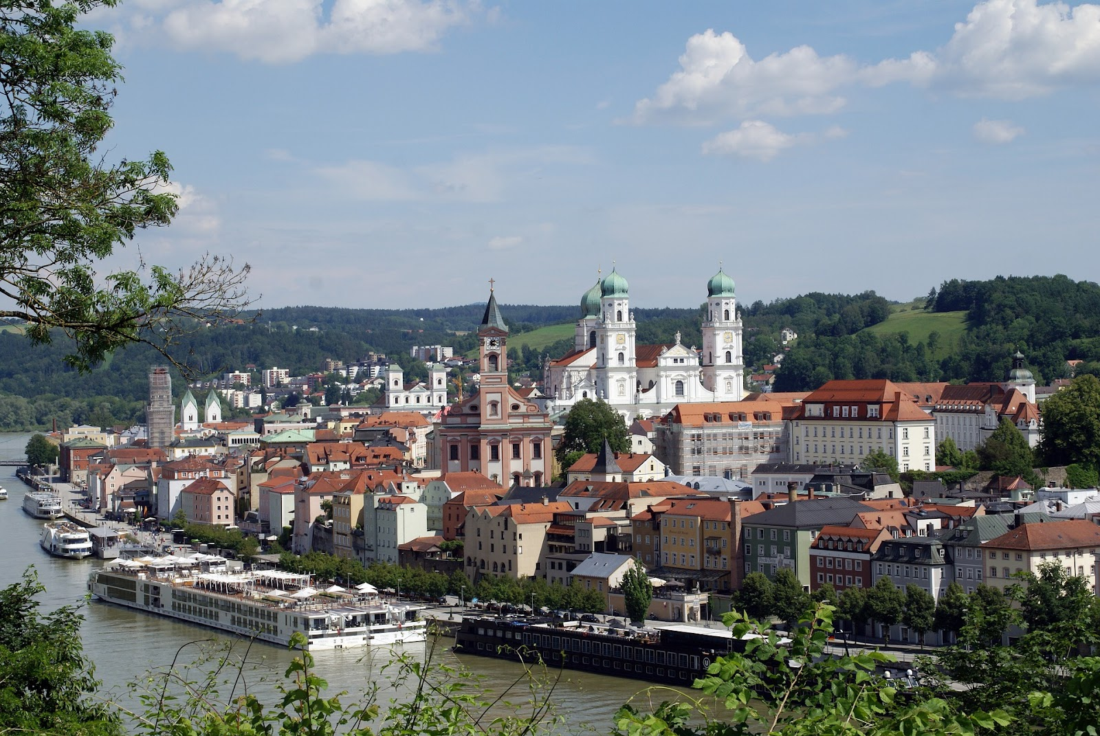 passau small old town medieval buildings and white decorative church seen from across river with cruise boats