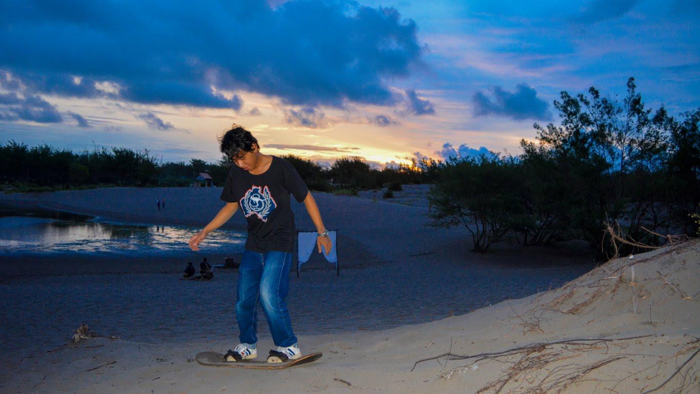 Bermain sanboarding saat matahari terbenam