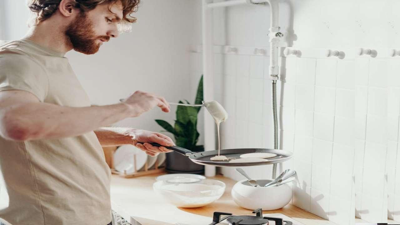 A person preparing food in a kitchen Description automatically generated