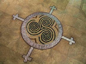 """Photo: RITE OF SIGNING MEDALLION 'NEW GRANGE-TRINITY'  """"In Nomine Patris et Filii et Spiritus Sancti - Amen""""  Carved metal and stone mosaic; ca. 80"""" x 80"""" St. Martha Catholic Church (Vestibule), Murrieta, CA"""