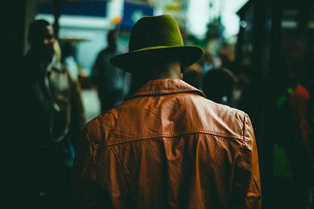 Dark image of a man's back. He is wearing a brown leather jacket and a green hat. The background is blurred, but people are still visible.