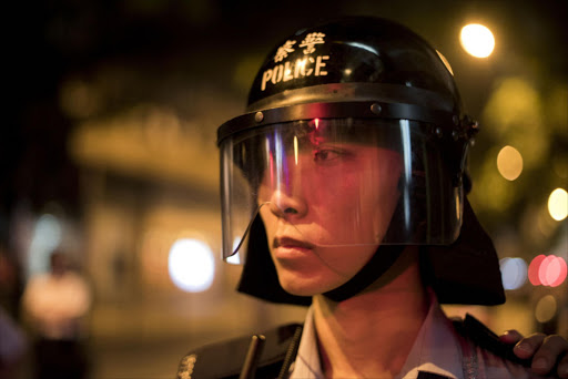 A police officer looks at a line of pro-democracy protesters rallying in the Wan Chai district of Hong Kong. Picture: AFP/ALEX OGLE