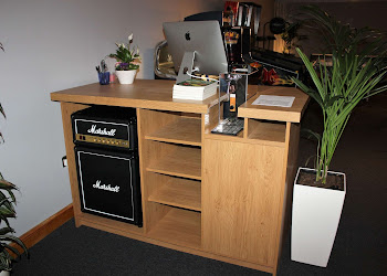 Premium Bar Design with an Amp in the shelves, a computer on the bar and a plant next to it