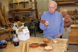 Photo: Bill Long looks over small bowls brought in for display by Panelist Chuck Engstrom, with pottery by Panelist Sally Giarratana on the left.