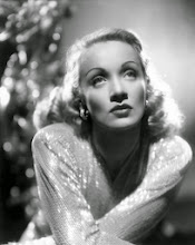 Photo: Here the skin is similarly treated.  And the artifice of the eyebrows is even more apparent.  Lighting of the hair emphasizes its luster. And again the fabric fascinates by catching light.  A background element is similarly visually engaging, but thrown out of focus to maintain emphasis on the star.  The star's gaze does not address the viewer directly; rather, the actress (Marlene Dietrich) allows herself to be gazed upon.