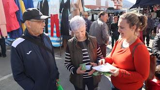Usuarios del mercadillo recibiendo los folletos informativos.