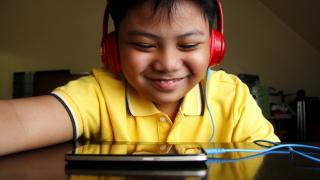 un niño sonriendo a la pantalla de un tablet