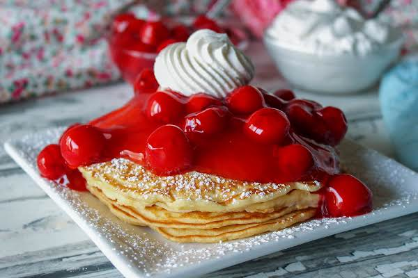 A Stack Of Cherry Vanilla Pancakes With Whipped Cream On Top.