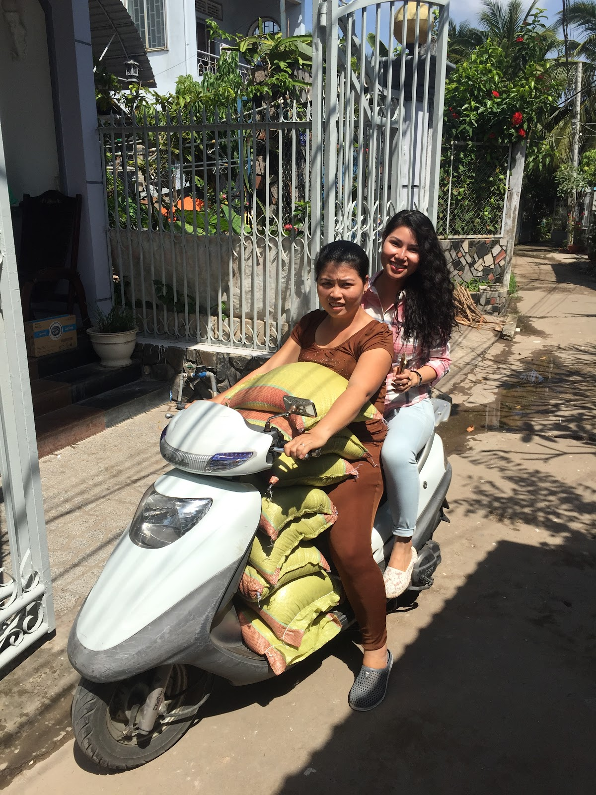 Female Riders carrying sacks on their motorcycle
