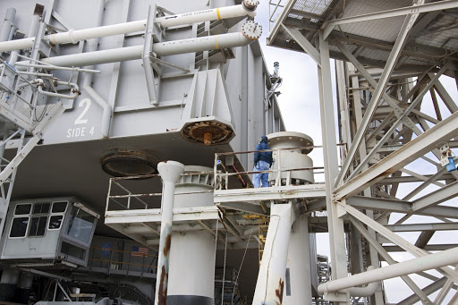 A technician monitors as No. 2 moves a space shuttle era mobile launcher platform over a support pedestal at Launch Pad 39A.