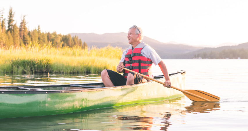 A retired man in a canoe on a lake