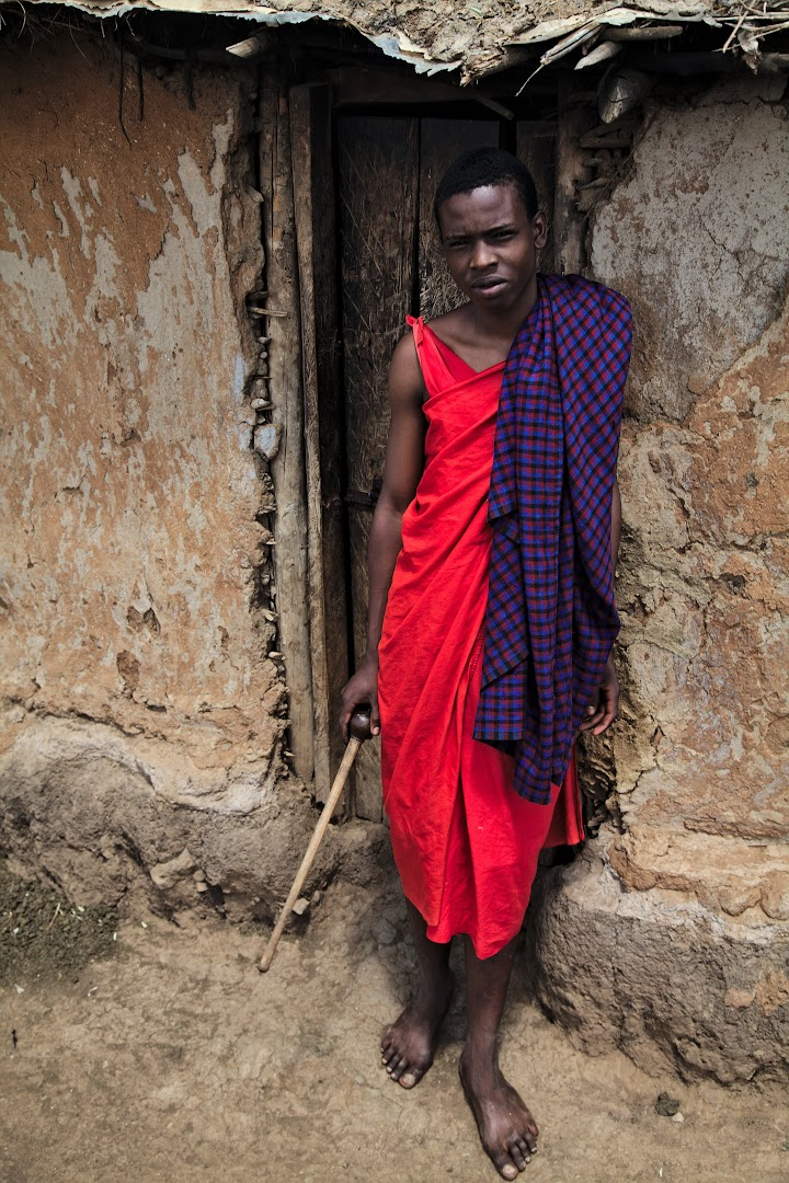 Young Masai in front of his mother's hut