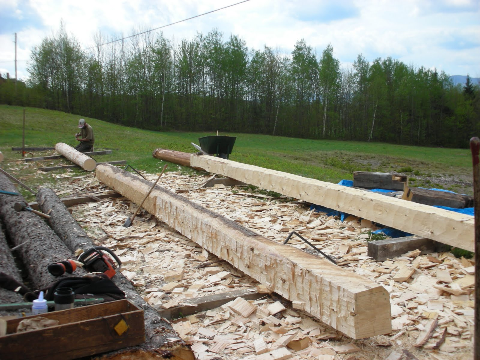The finished sill timber is in the background with a new sill being roughed out in the foreground.  Michael begins laying out a post timber from a log.