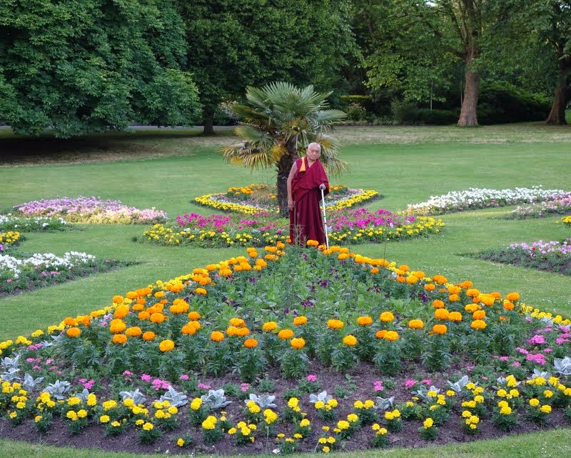 """Lama Zopa Rinpoche in a park in Leeds offering all the flowers to the """"gurus and buddhas, statues, stupas and scriptures, etc., etc.,"""" according to Ven. Roger Kunsang, UK, July 2014. Photo by Ven. Roger Kunsang."""