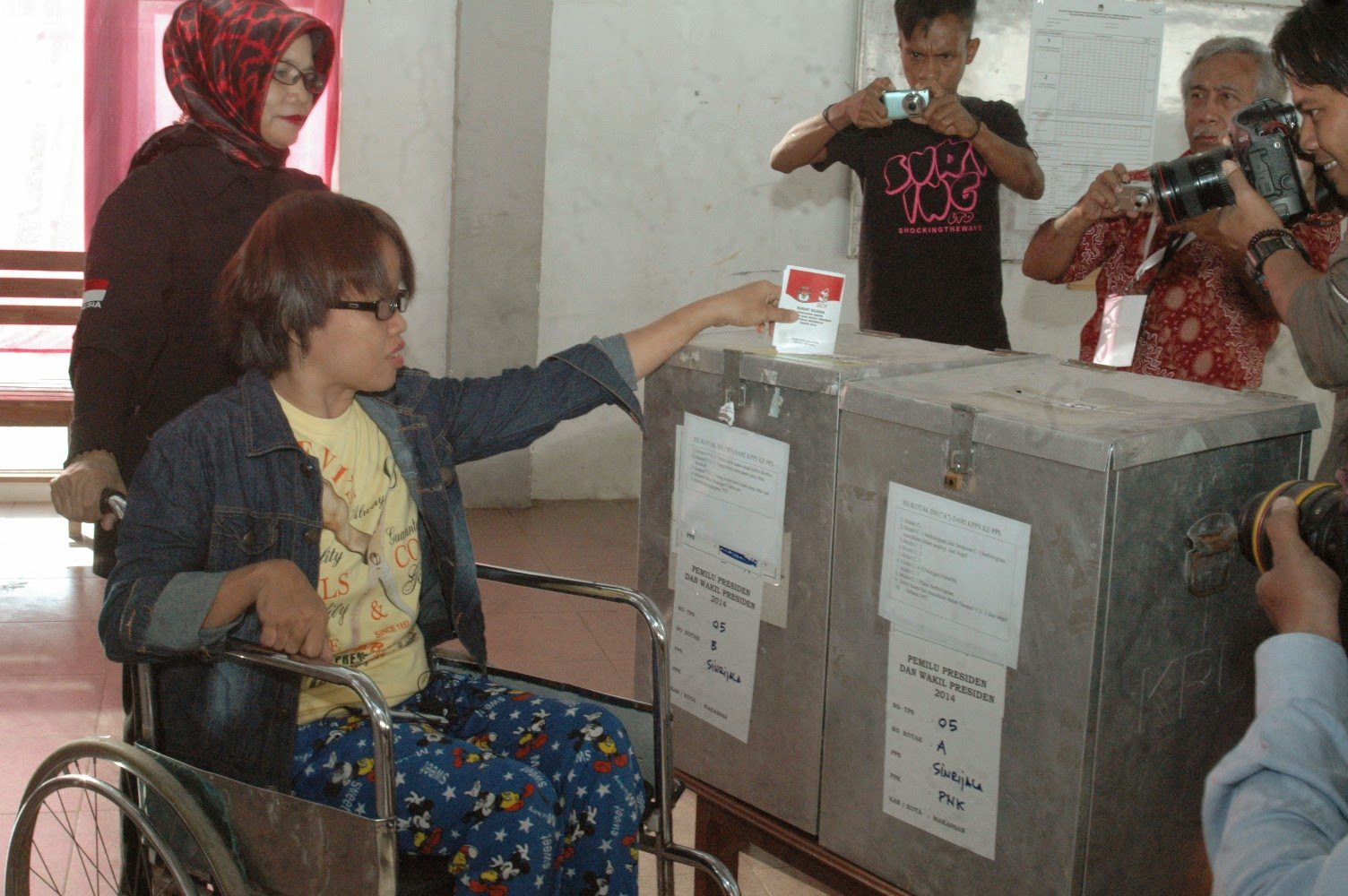 Wheelchair voter is assisted by a KPPS member and is insrting her ballot paper in South Sulawesi