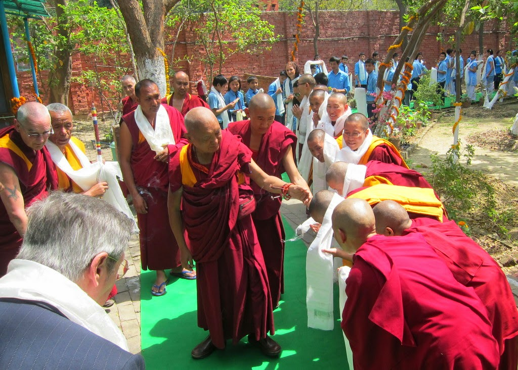 Lama Zopa Rinpoche being greeted by the nuns of Tara Nunnery, a project of Kopan Nunnery, and the children of Alice Project Universal Education School, Sarnath, India, March 2014. Photo by Ven. Sarah Thresher.
