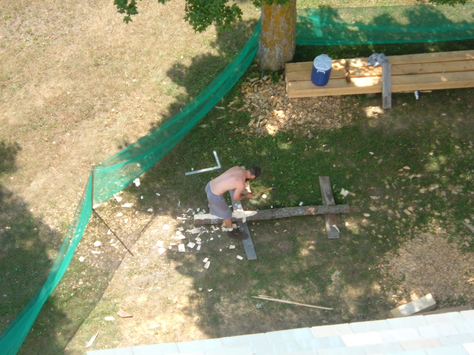 Seth Kelley is seen from the bell deck adzing out one of the new hip rafters.