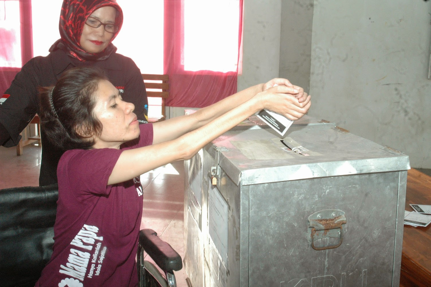Wheelchair voter is inserting her ballot paper independently in South Sulawesi
