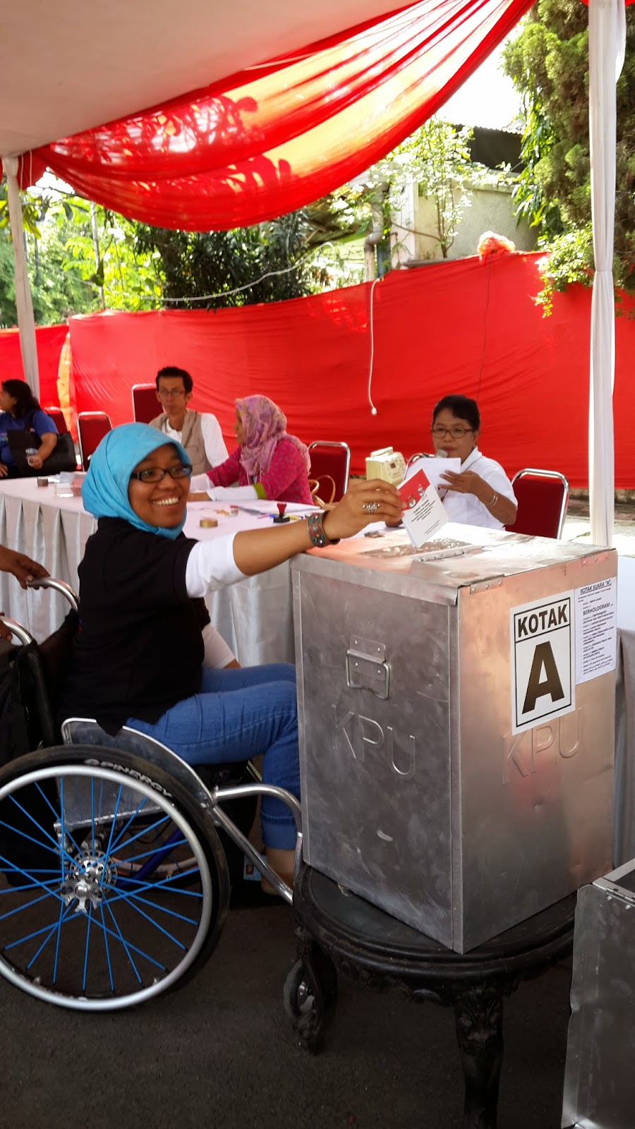 Phisicaly impaired voter inserting her ballot paper in Jakarta