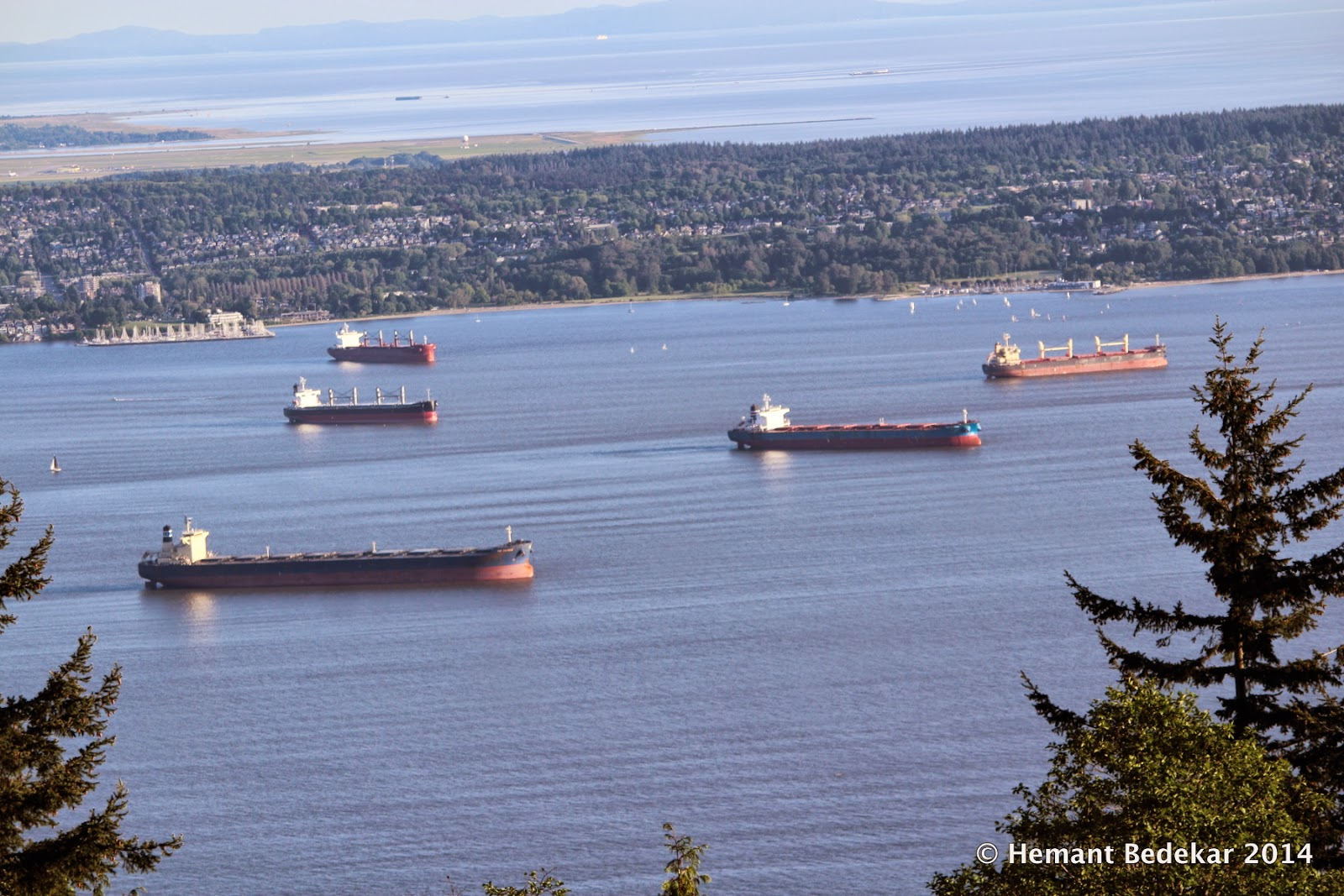 Container ships and vessels waiting for their turn to dock into the port of Vancouver