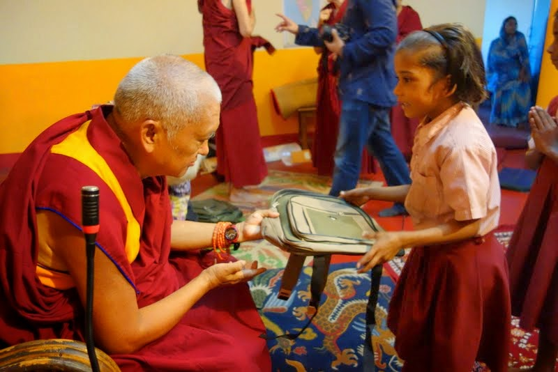Lama Zopa Rinpoche offering rucksacks to young Maitreya School students, Bodhgaya, India, March 2014. Photo by Ven. Roger Kunsang.