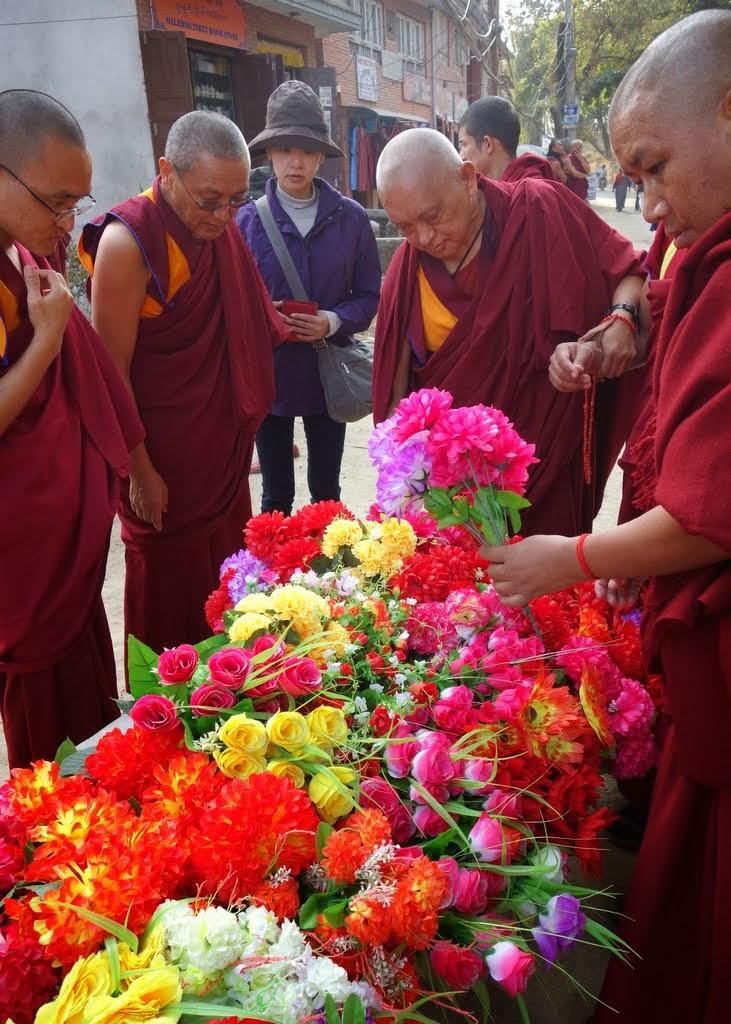 Lama Zopa RinpochebuyingplasticflowerswhilecircumambulatingSwayambhuStupawithKhenRinpocheGesheChonyi and GesheJangchub,Kahtmandu, Nepal, November 24, 2013.Photo byVen. RogerKunsang.