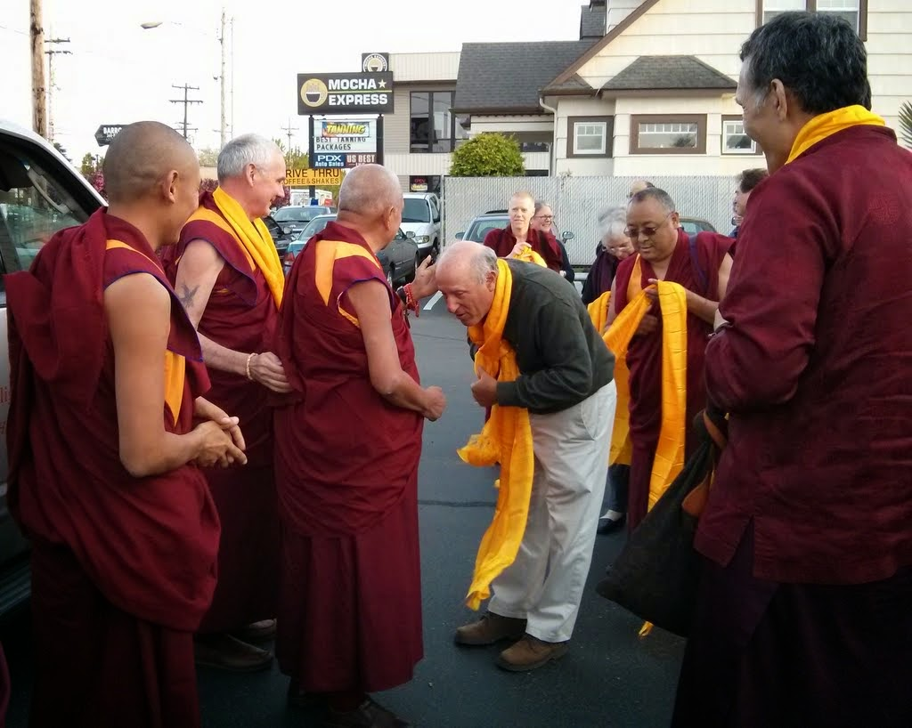Lama Zopa Rinpoche, having just arrived in Portland, being greeted by Yangsi Rinpoche (far right); Karuna Cayton, chair of the FPMT Inc. Board of Directors; and other board members and staff of International Office and Maitripa College, Portland, Oregon, US, April 2014. Photo by Mandala.