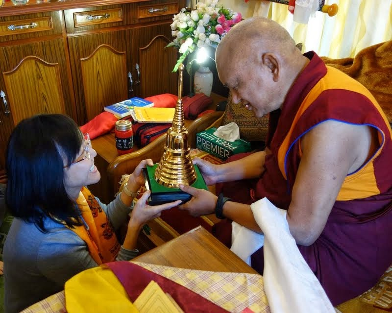Lama Zopa Rinpoche being offered a relic of Lama Atisha, Sera Monastery, India, December 2013. Photo by Ven. Roger Kunsang.