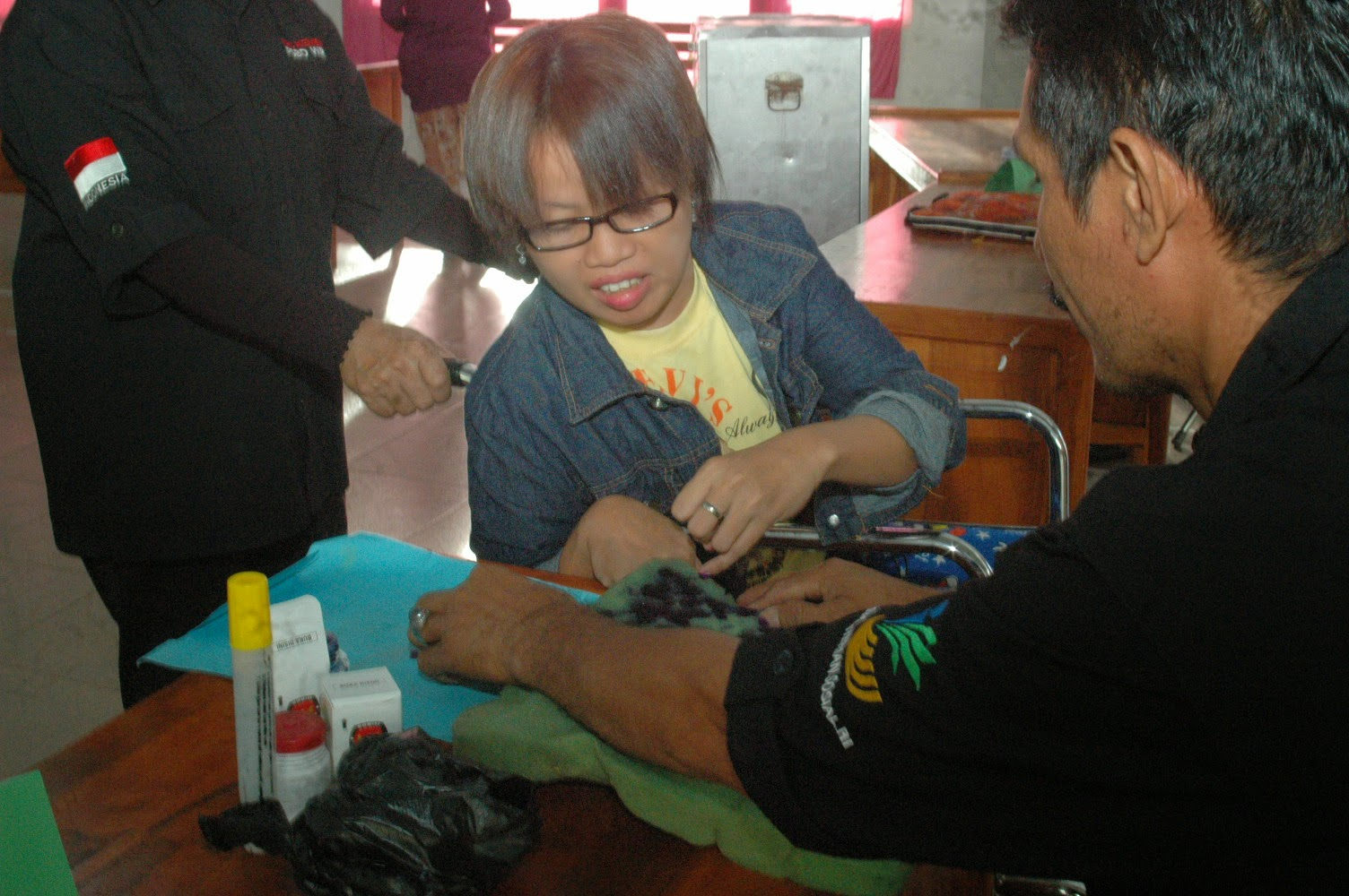 Wheelchair voter is marking her finger in South Sulawesi