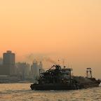 The non-postcard Hong Kong - industrial barges riding between Kowloon and Hong Kong Island at dusk, polluting the air