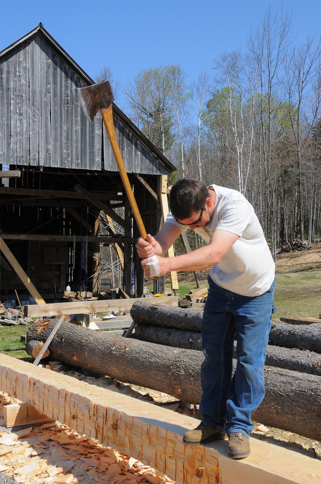Seth Kelley scores the timber with a felling axe before making a final pass with the broad axe