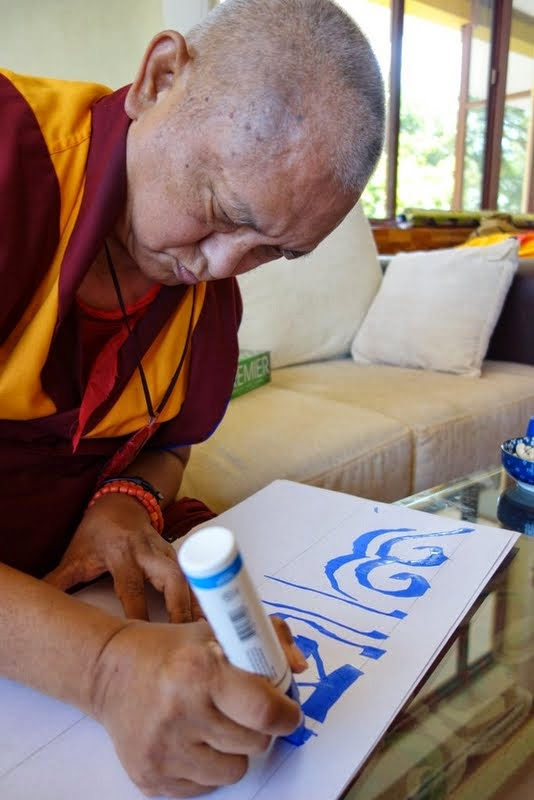 Lama Zopa Rinpoche writing the special mantra Om Pema Ushnisha Bimala Hum Phat, which will go above where all the white rabbits live at Osel Labrang, Sera Je Monastery, India, January 2014. Photo by Ven. Roger Kunsang.