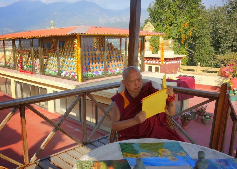 Lama Zopa Rinpoche reads prayers after lunch on the top floor of Kopan Monastery with 1,000 buddha statues behind and the mountains in the distance, Nepal, November 23, 2013. Photo by Ven. Roger Kunsang.