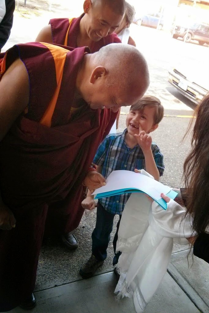 Lama Zopa Rinpoche being offered a hand-traced copy of the Heart Sutra by Dechen, a young student of Rinpoche, Portland, Oregon, US, April 2014. Photo by Mandala.