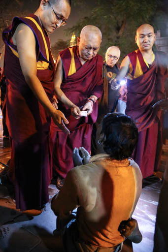 Lama Zopa Rinpoche offering to a beggar, Mahabodhi Stupa, Bodhgaya, India, February 2015. Photo by Ven. Thubten Kunsang.