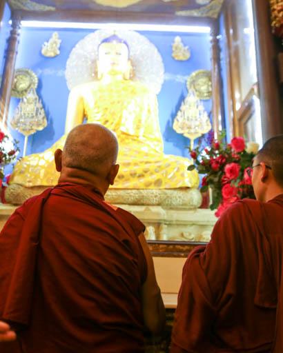 Lama Zopa Rinpoche in front of Buddha statue at Mahabodhi Stupa, Bodhgaya, India, February 2015. Photo by Ven. Thubten Kunsang.