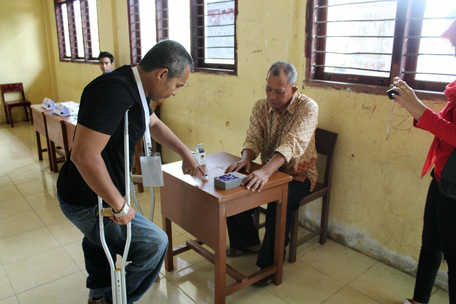 Physically impaired voter dipping his finger in Aceh