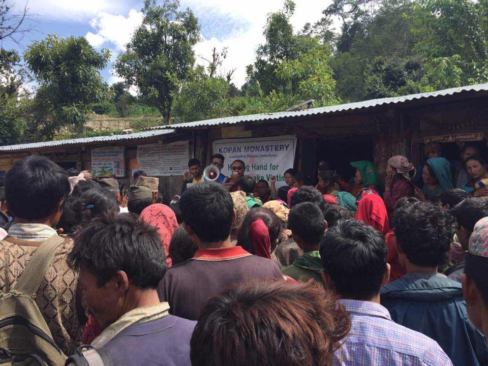 Kopan Helping Hands making announcements and delivering aid.