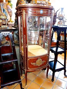 Очень изящная витрина с изумительной тонкой работы бронзой. 19-й век. Одна двернка, резная позолоченная бронза, одна фарфоровая плашка в стиле Веджвуд. На дверке большой центральный медальон из золочёной бронзы. 67/40/151 см.