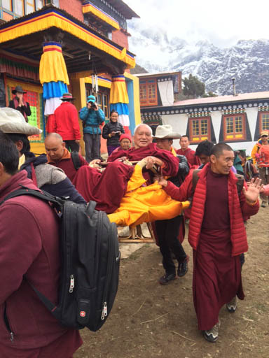 Lama Zopa Rinpoche being carried from Lawudo Retreat Centre down to Thamu Gompa, Nepal, April 2015. Photo by Harry Sutton.