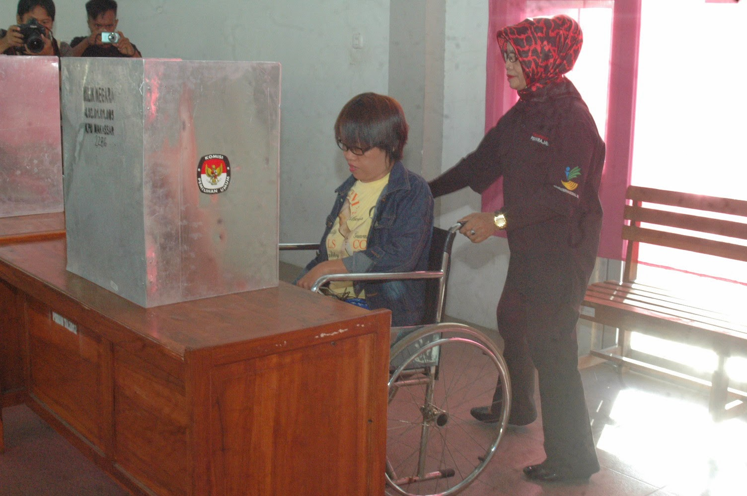 Wheelchair voter is assisted by a KPPS member (2)