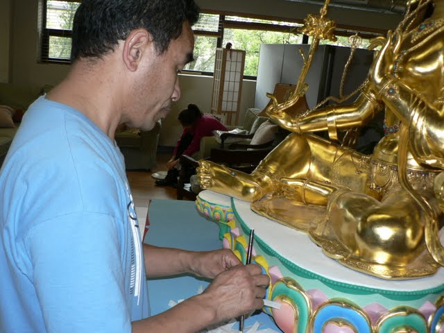 Gelek adds gold leaf to base of Red Tara statue, April 2011, FPMT International Office, Oregon, USA