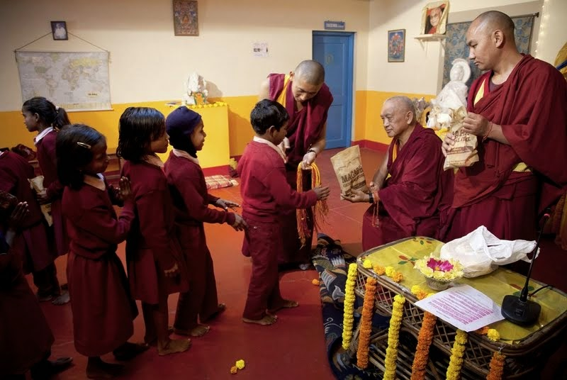 Lama Zopa Rinpoche offering gifts to children from Maitreya School and Tara Children's Home at Root Institute, Bodhgaya, India, March 2014. Photo by Andy Melnic.