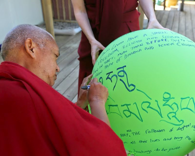 Lama Zopa Rinpoche writing mantras on a helium balloon, Kachoe Dechen Ling, Aptos, California, May 2014. Photo by Ven. Thubten Kunsang.